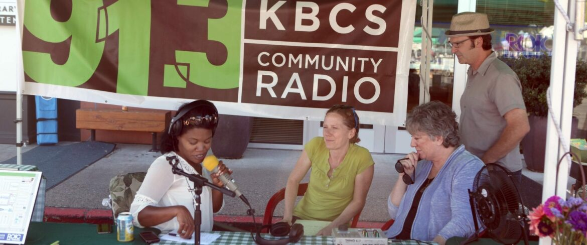 Sonya Green, news and public affairs director at 91.3 KBCS (left), interviews Sue Popma, marketing director of the Crossroads Shopping Center, and Roz Liming, Crossroads marketing manager, during a live broadcast from the Crossroads Farmers Market in August, as Bruce Wirth, KBCS program manager, looks on.