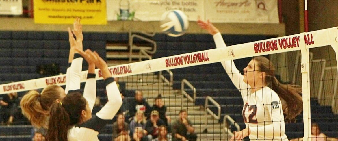 A Bellevue College volleyball player hits the ball at the net