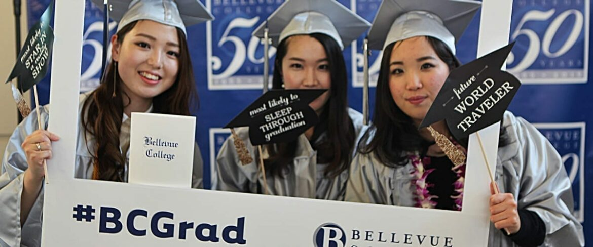 Three Bellevue College students in cap and gown pose inside the oversized #BC Grad picture frame