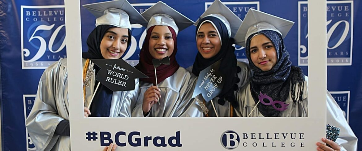 Four Bellevue College students in cap and gown pose inside the oversized #BC Grad picture frame