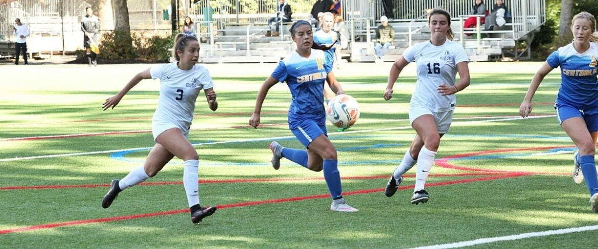 Two Bellevue women's soccer players on the attack against a defender