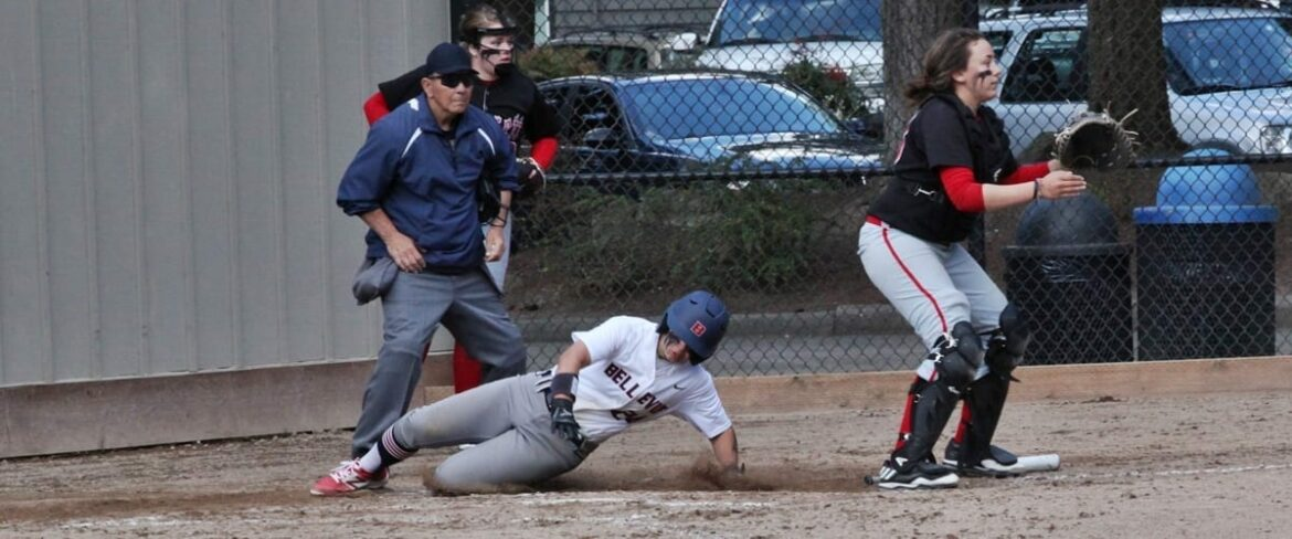 A Bellevue College softball player slides across home plate behind the Everett CC catcher