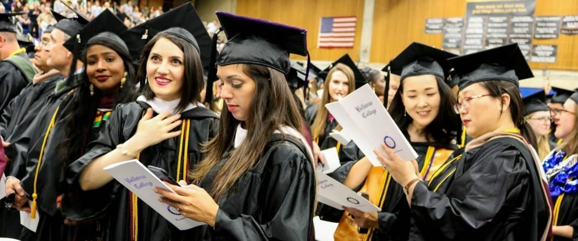 BC graduates in caps and gowns read the commencement program