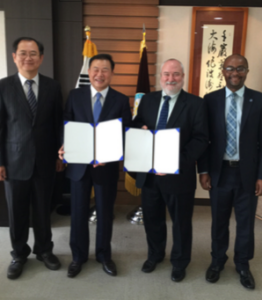 Dave Rule and Jean D'arc Campbell posing with Memorandum of Understanding agreements with counterparts in Asia