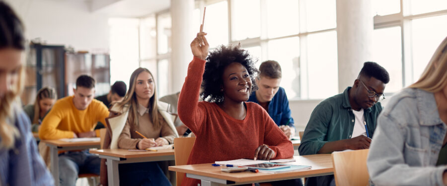 Female student in classroom with her hand raised