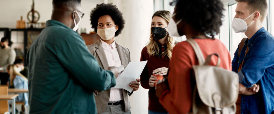 Teacher and students talking, while wearing masks