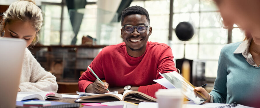 Portrait of smiling black student in library with classmates studying.