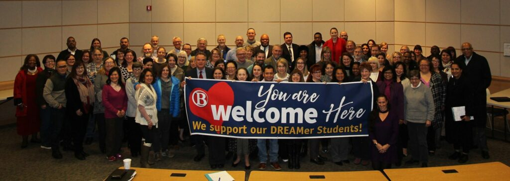 Administrators holding You are welcome here banner