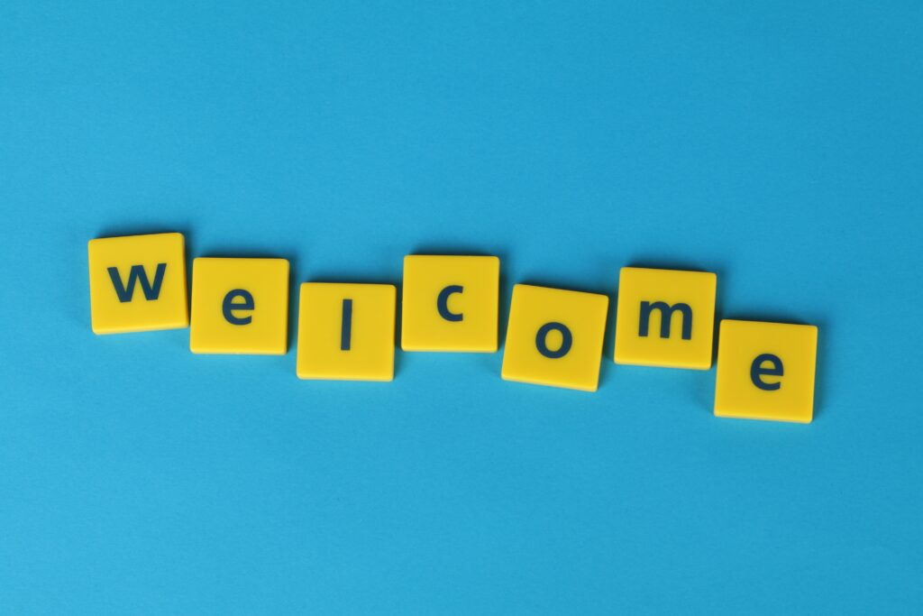 blue background with yellow tiles spelling welcome in black text
