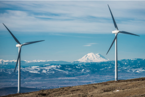 Two wind turbines with a view of the mountains covered in snow