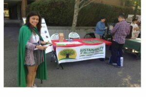 Sophia in green cape signing up volunteer student