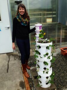 Karrin stands next to upright gardening buckets