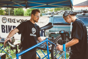 Two Bike Works Volunteers are working on a bike that is on a bike stand. A Bike Works banner is in the background.