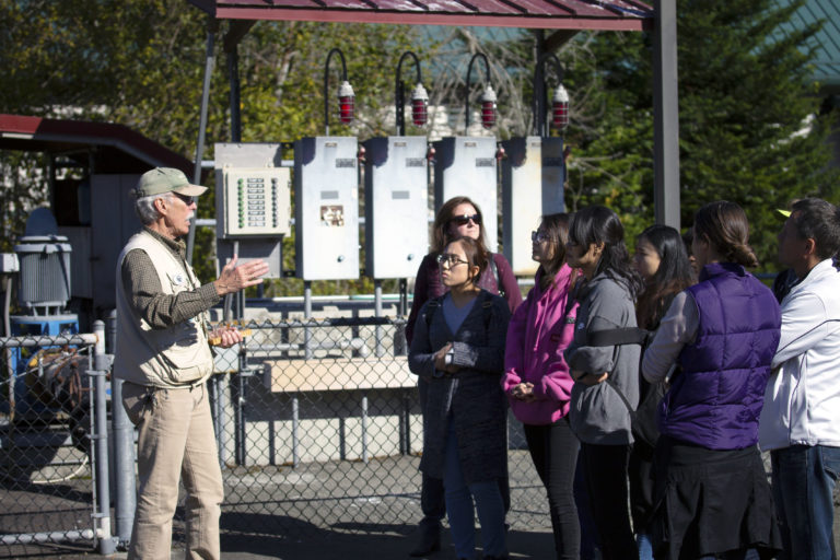 A tour guide talking to students during a sustainability field trip to the issaquah salmon hatchery