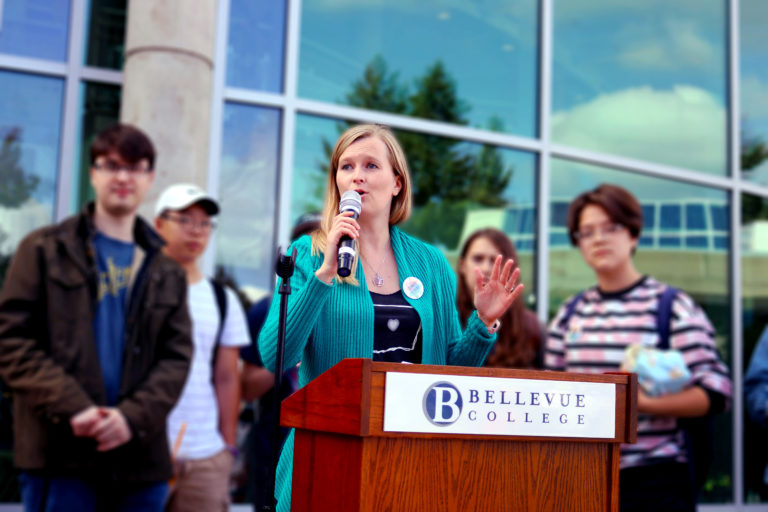 Bellevue College's director of sustainability speaking at a podium.