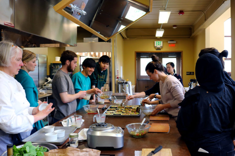 Students cooking organic food during a sustainability field trip to 21 Acres Farm