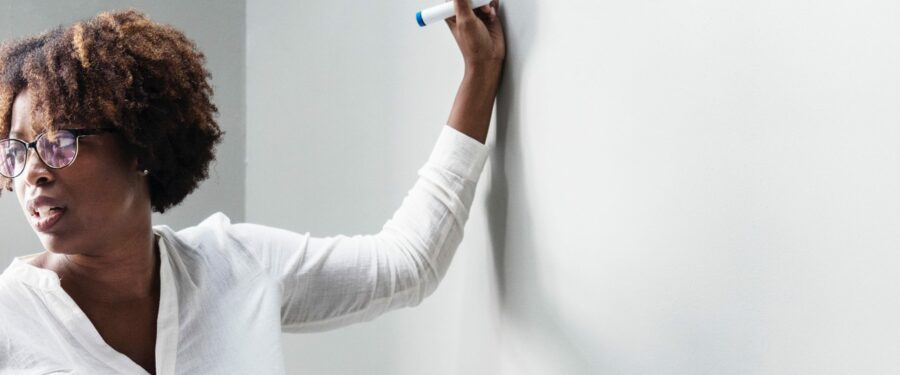 photo of teacher in front whiteboard, getting ready to write something