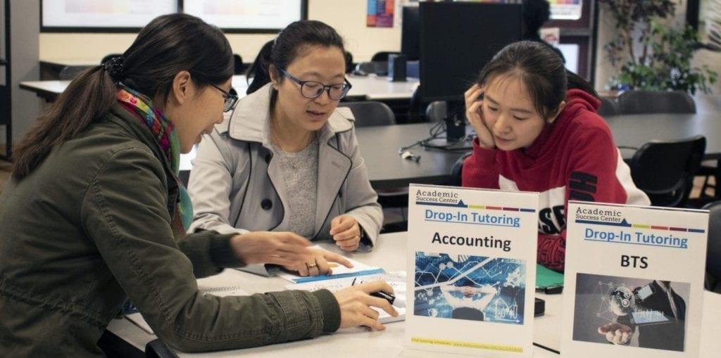 Three students tutoring at a table