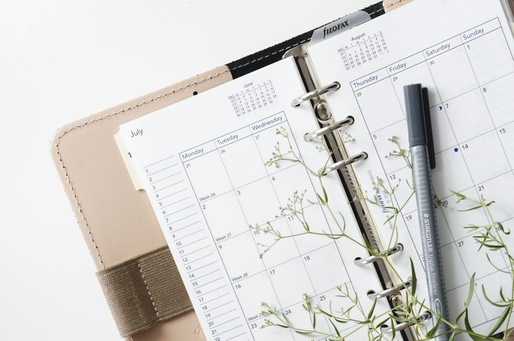 Close view of a planner calendar with a pen and a sprig of green plant