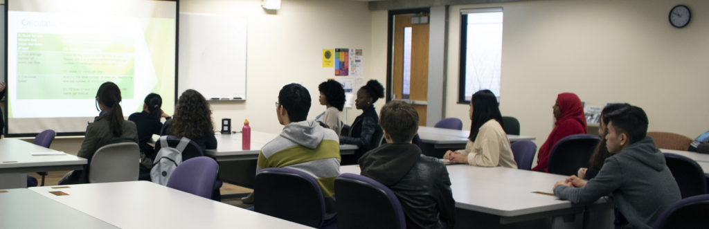Students in a classroom are looking at a presentation on a projector screen