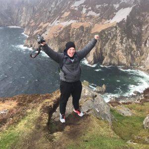 Program alumni, Jesse, posing on a rock in Donegal Ireland