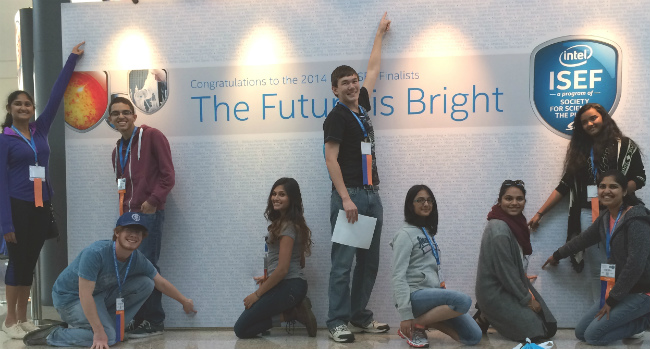 2014 ISEF participants point to their name on the Name Board.