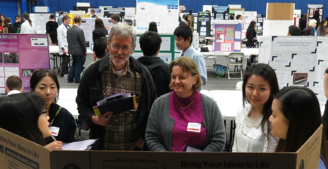 Smiling judges gather around student presenting project.