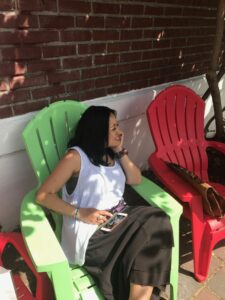Donna Miguel sitting in the shade in a large green chair