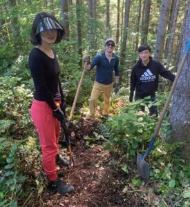Three people with shovels in the forest