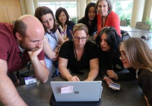 Bellevue College faculty gathered around a laptop