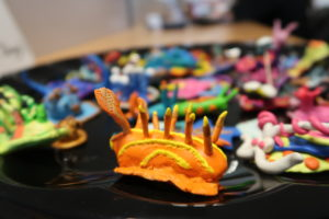 Image of clay orange nudibranch as made by students as a part of Making Learning Visible, as a link to the