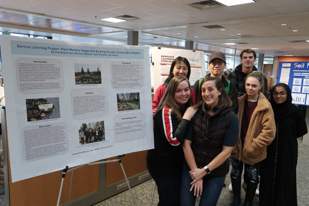 Group of people posing next to a poster