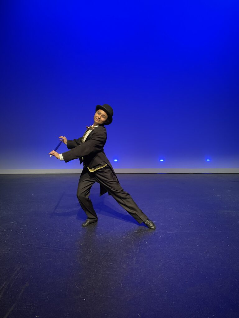 Student in black tuxedo and top hat making an artistic dance pose on a stage with blue background