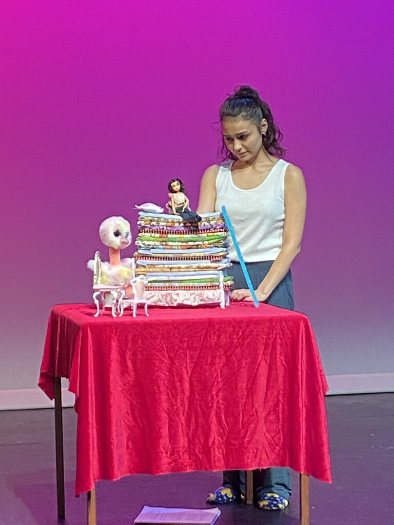 Student looking down at an doll on top of small mattresses all on a red-covered table with a purple background.