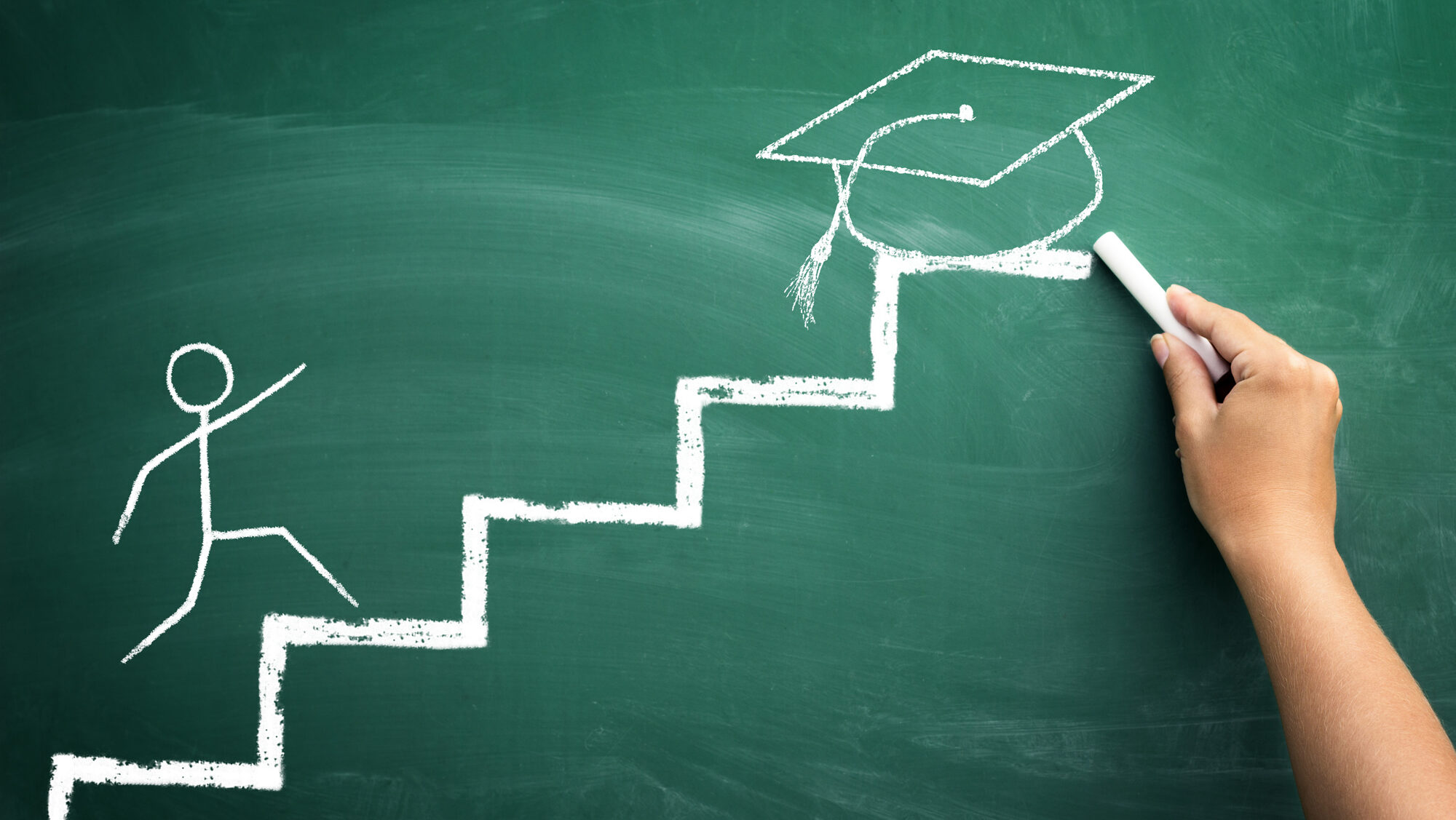 Green chalk board with stick figure climbing stairs to graduation cap.