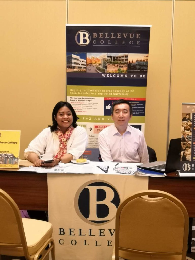 The assistant director of international recruiting and his assistant at a recruitment fair in front of the BC table.