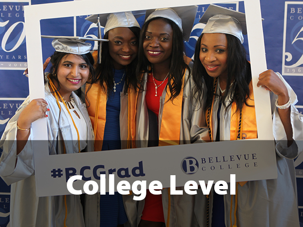 College-level. Picture of four students at graduation in a cap and gown holding a photo frame that says BC Grad.