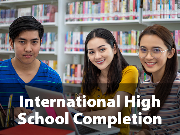 International High School Completion. Picture of three students sitting at a table at  the library.