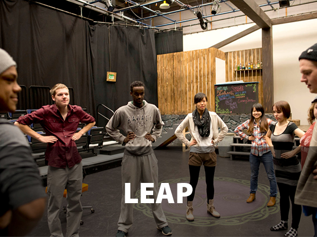 LEAP. Students in a theater class standing in a circle with their hands on their hips. Black curtain backdrop and a chalk board.