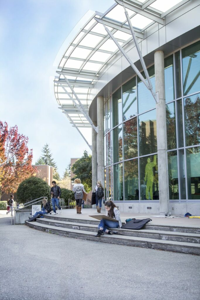 Photo of the C building with students walking in front and an art student drawing on the steps.