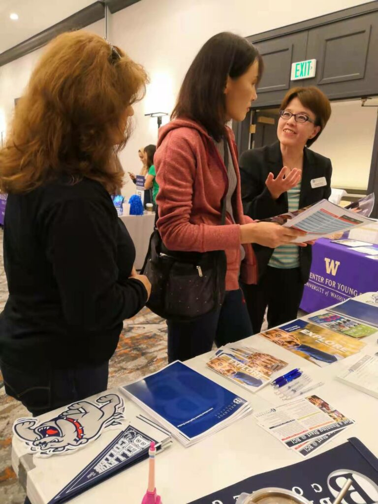 Three people holding Bellevue College brochures talking over a table at a recruitment fair.