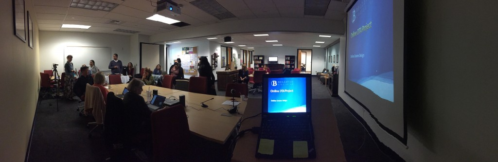 A panorama shot of Faculty Commons that encompasses the whole room and all the people attending. Sue Cox is in the left corner, standing and speaking to the room. In the right corner of the picture is the presentation screen with the words, Online DTA Project, as the title of the presentation.