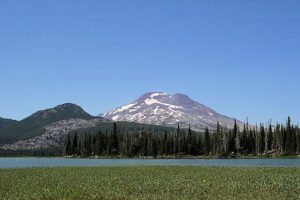Photograph of a mountain behind a lake and open meadow.