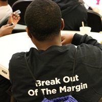 The back of a BOOM participant's shirt that says Break Out Of The Margin