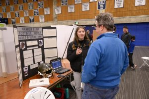 A woman talks to a man during the Science Fair
