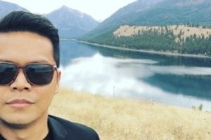 Daniel Cruz poses in front of mountains and a lake