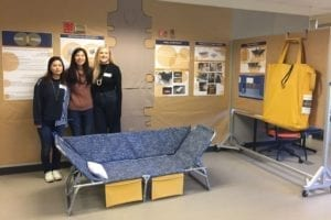 Three female studentsin a prototype shelter