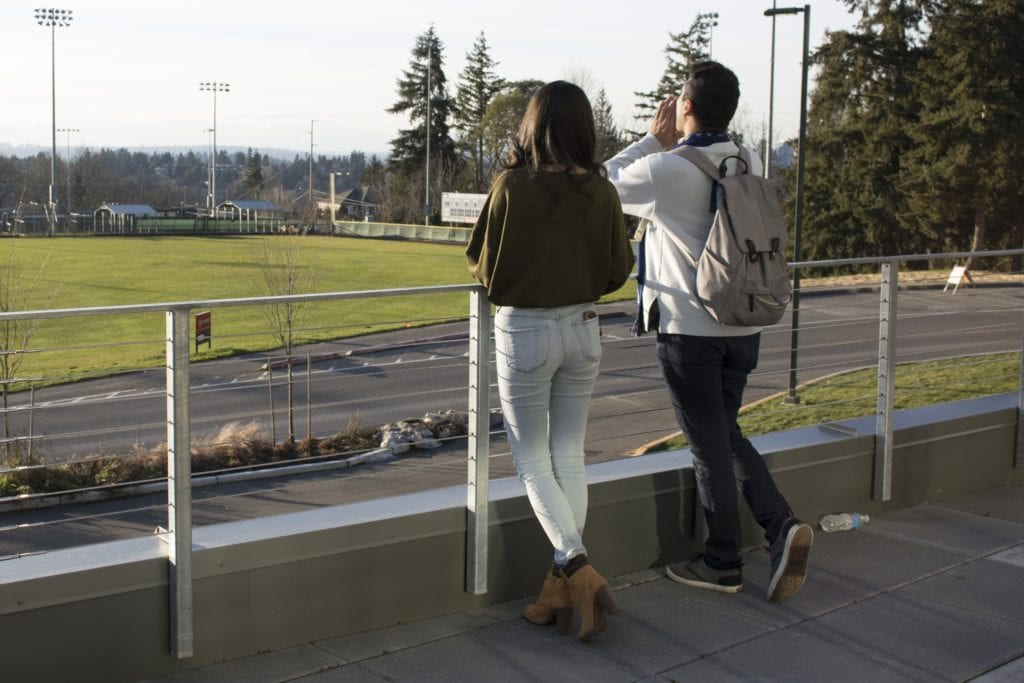 One female student and one male student leaning against a chain link fence