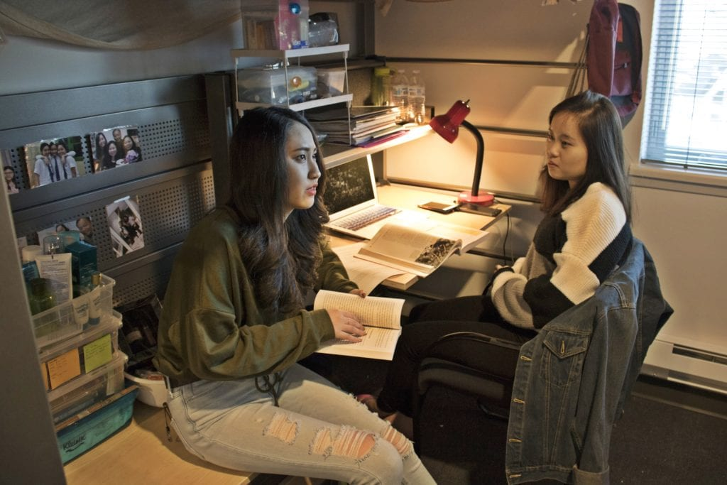 Two female students inside a residence hall unit