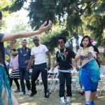 students learning traditional dance at outdoor party